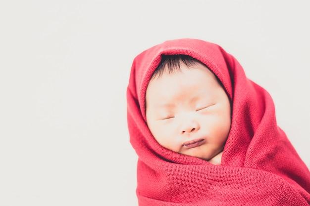 Bebê recém-nascido em daiper vermelho dormindo na cama