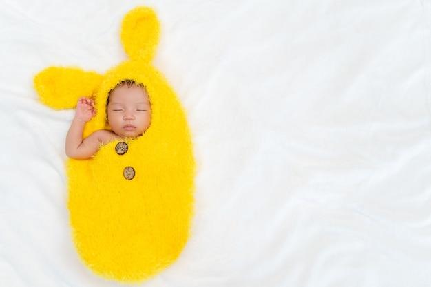 Bebê recém-nascido em terno de pele de coelho dormindo em uma cama
