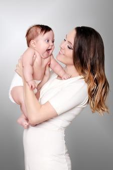 Bebê recém-nascido em um abraço terno da mãe na janela