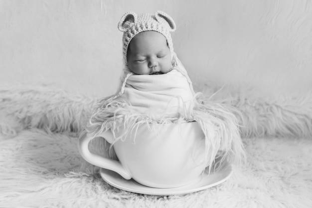 Bebê recém-nascido em uma xícara de chá grande. conceito de infância, saúde, fertilização in vitro, bebidas quentes, café da manhã