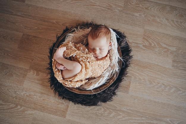 Bebê recém-nascido embrulhado em um cobertor, dormindo em uma cesta. conceito de infância, saúde, fertilização in vitro. foto em preto e branco