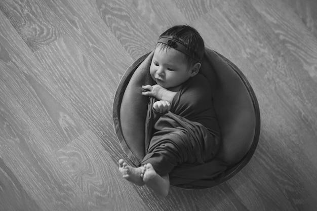 Bebê recém-nascido embrulhado em um cobertor, dormindo em uma cesta. conceito de infância, saúde, fertilização in vitro. preto e branco