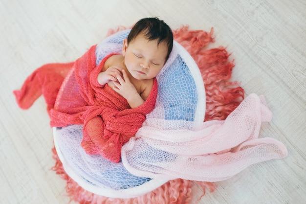 Bebê recém-nascido envolvido em um cobertor que dorme em uma cesta. conceito de infância, cuidados de saúde, fertilização in vitro