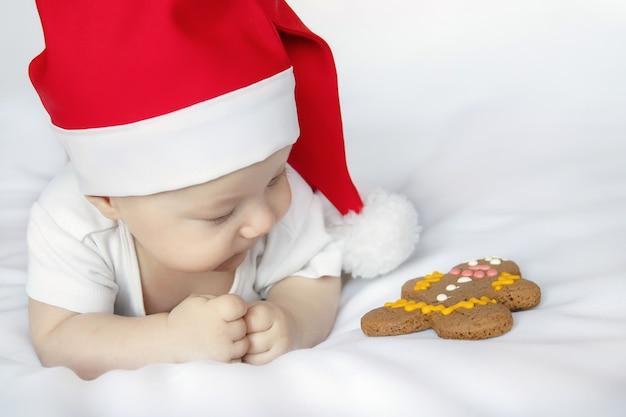 Bebê recém-nascido fofo com fantasia de papai noel de natal com mentira no lençol branco e olhando para um pão de mel