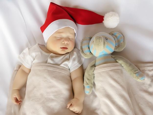 Bebê recém-nascido fofo com fantasia de papai noel dormindo em um lençol branco com um brinquedo de pelúcia, vista superior