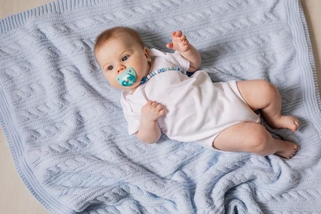 Bebê recém-nascido fofo com uma chupeta na boca e um macacão branco, deitado de costas sobre um cobertor azul