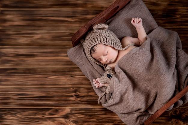 Bebê recém-nascido, lindas mentiras infantis e segurando um pequeno ursinho de pelúcia na cama no fundo de madeira, espaço de cópia.