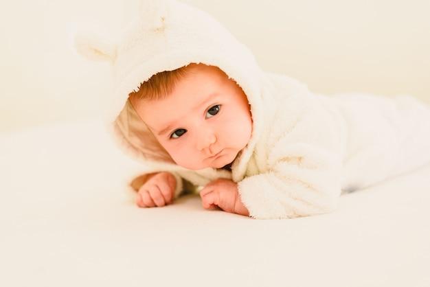 Bebê recém-nascido loira 3 meses de idade deitado de bruços e cabeça levantada
