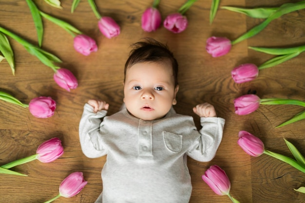Bebê recém-nascido menino ou menina encontra-se entre tulipas e olhando para o quadro. ótimo cartão de felicitações