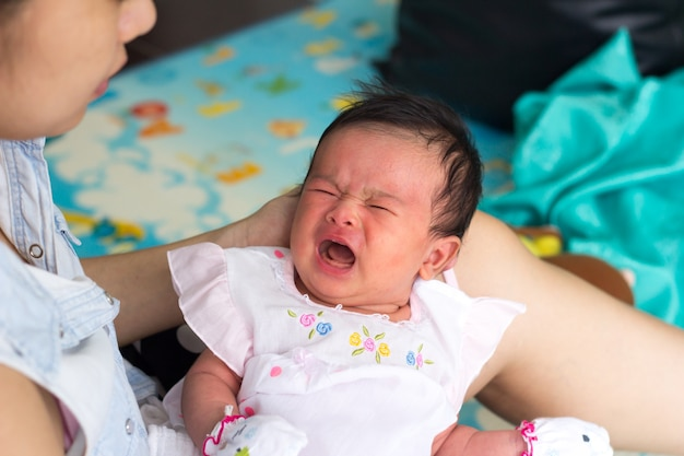 Bebê recém-nascido nas mãos da mãe. mãe segurando a cabeça de seu bebê recém-nascido nas mãos.
