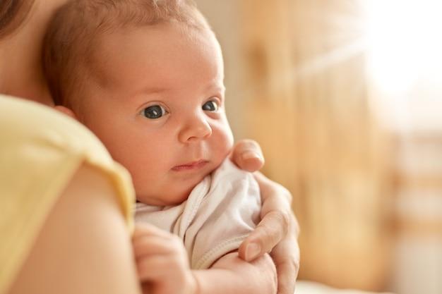 Bebê recém-nascido nos braços da mãe, olhando para longe e estudando as coisas exteriores, mãe sem rosto com criança dentro de casa, lindo bebê com mãe.