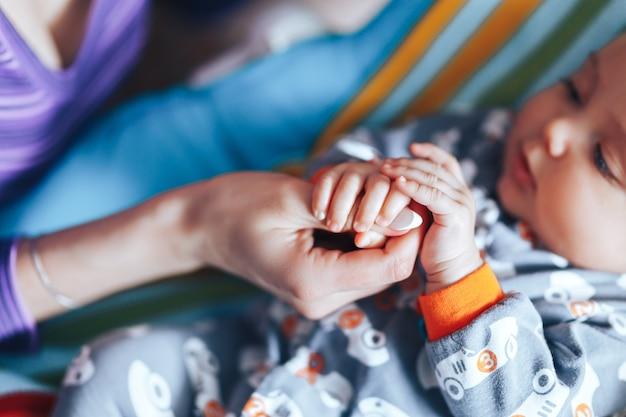 Bebê recém-nascido segurando uma mão do pai