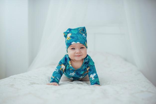 Bebê recém-nascido vestido com um terno verde, deitado em uma cama macia