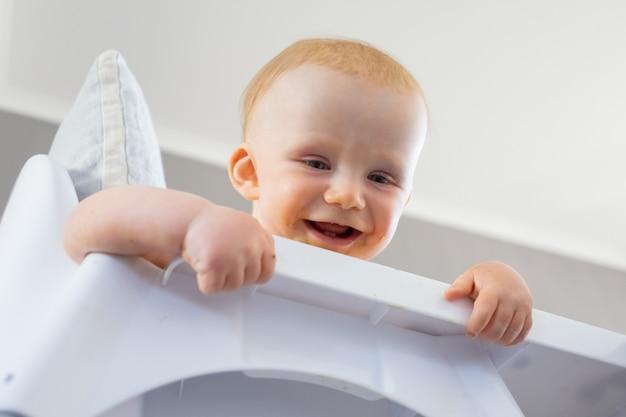 Bebê ruivo feliz olhando para o chão da cadeira alta, sorrindo e rindo. ângulo baixo. processo de alimentação ou conceito de cuidado infantil