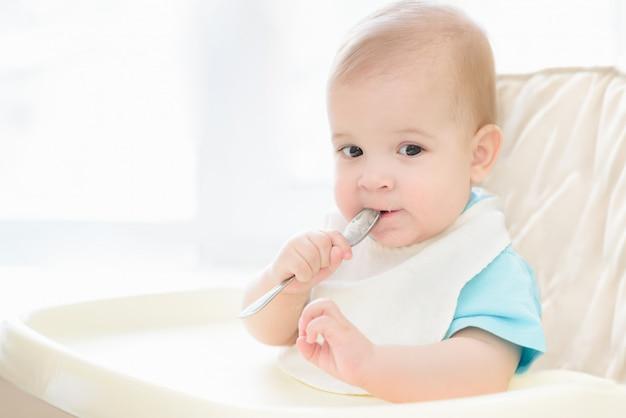 Bebê segurando uma colher na boca