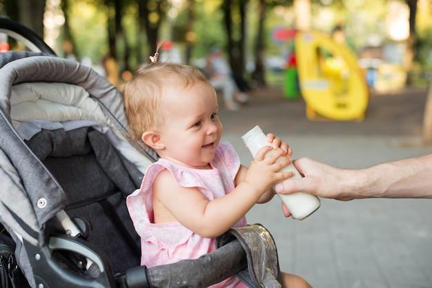 Bebê segurando uma mamadeira em um carrinho de bebê