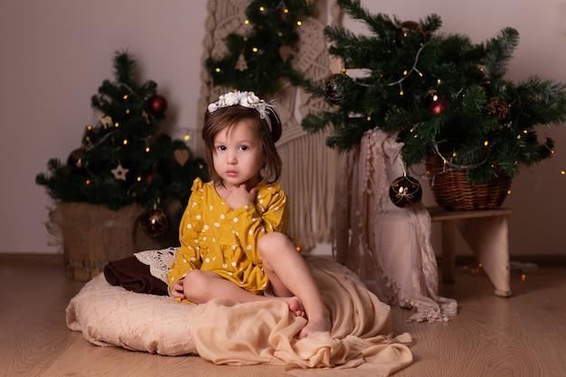 Bebê sentado ao lado da árvore de natal e luzes