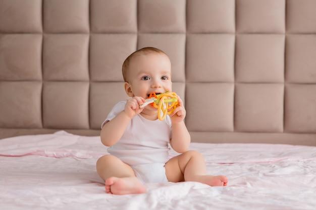 Bebê sentado com um brinquedo no quarto na cama