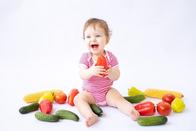 Bebê sentado com vegetais em um fundo branco isola o conceito da primeira isca