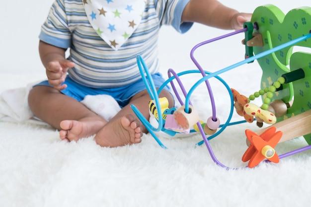 Bebê sentado e brincar de brinquedos de madeira, brinquedo de foco