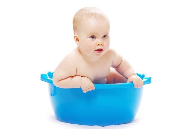 Bebê sentado em uma banheira azul