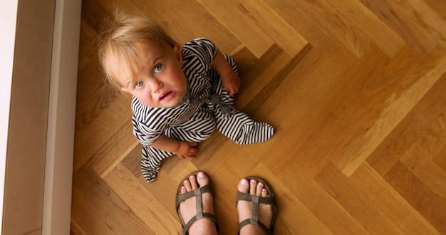 Bebê sentado no chão de madeira