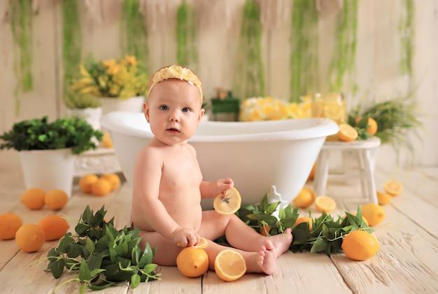 Bebê sentado rodeado de limões no banho