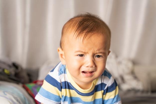 Bebê sentado triste e chorando no quarto
