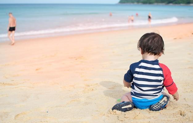 Bebê sente-se na praia jogando areia