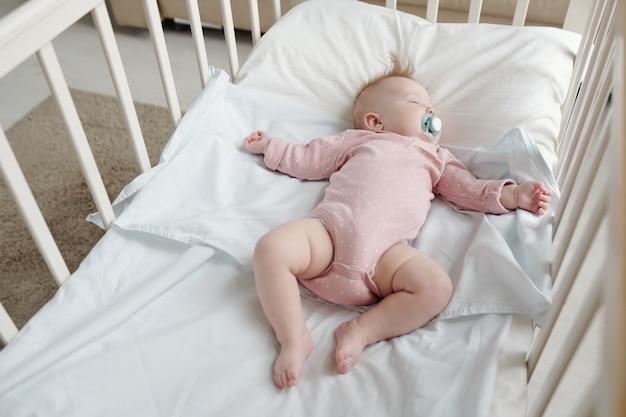 Bebê sereno com roupas rosa deitado sobre lençóis brancos no berço