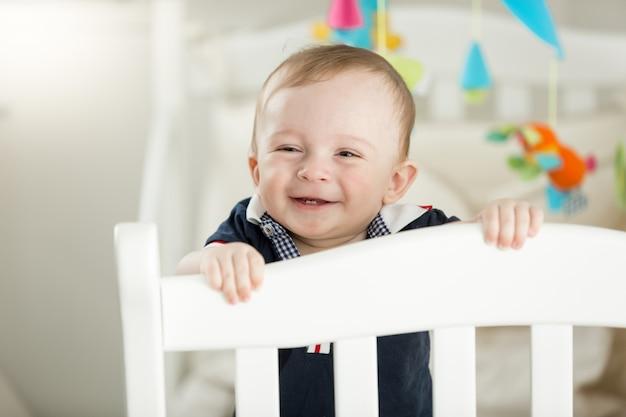 Bebê sorridente de 9 meses de pé em um berço de madeira branco