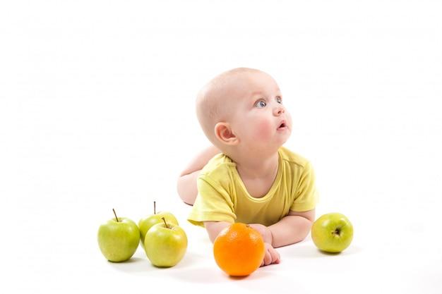 Bebê sorridente fofo deitado de bruços entre frutas e procurando