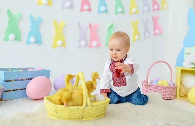 Bebê sorridente fofo no bordado tradicional em decorações de páscoa coloridas