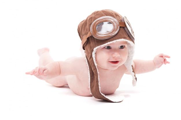 Bebê sorridente fofo nu na tampa do piloto está voando aw