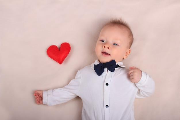 Bebê sorridente fofo usando smoking com coração vermelho de brinquedo