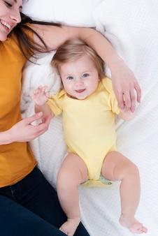 Bebê sorridente posando ao lado da mãe
