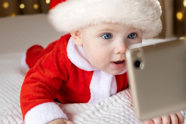 Bebê sorridente vestindo fantasia de papai noel vermelho fazendo videochamada para os avós no natal online.