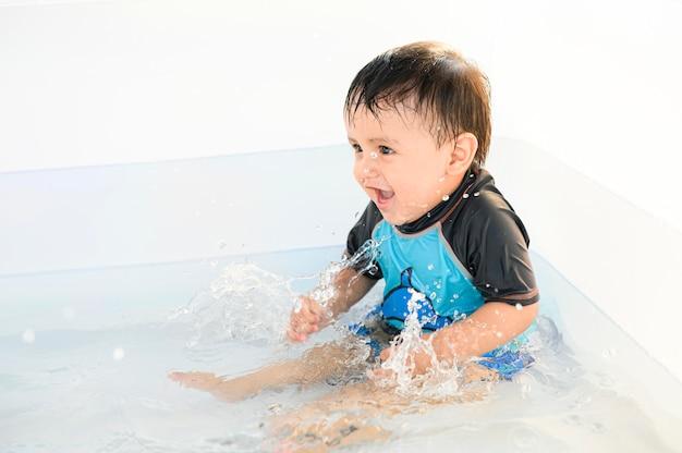 Bebê sorrindo e curtindo a água em uma piscina