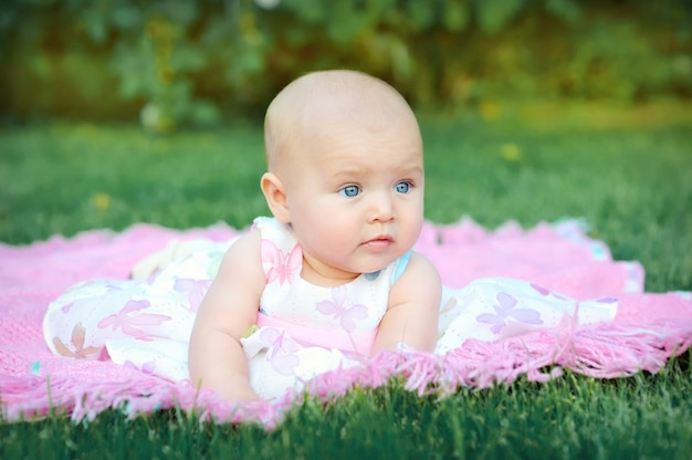 Bebê sorrindo e olhando para a câmera ao ar livre na luz solar.