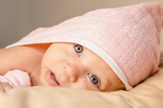 Bebê surpreendido com grandes olhos azuis e boca aberta deitada na barriga sob a toalha rosa após banho