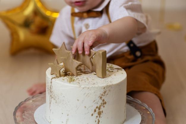Bebê toca um bolo de aniversário com estrelas