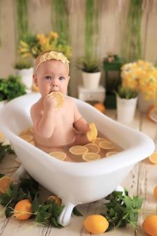 Bebê tomando banho com limões cercado de plantas