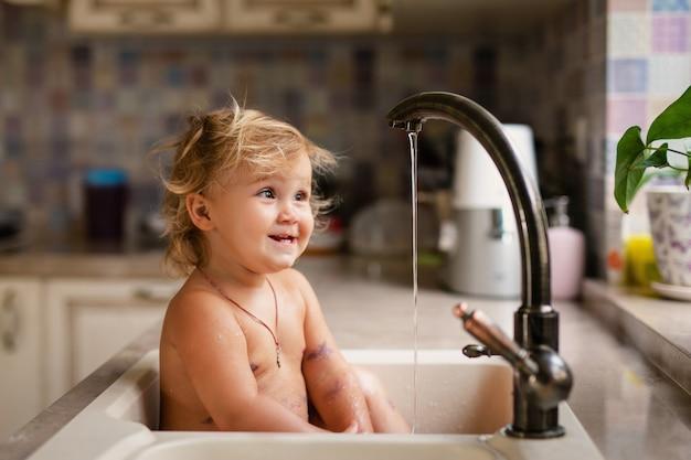 Bebê tomando banho na pia da cozinha. criança brincando com água na cozinha ensolarada com janela.