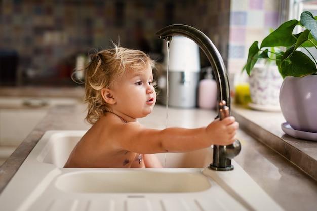 Bebê tomando banho na pia da cozinha.
