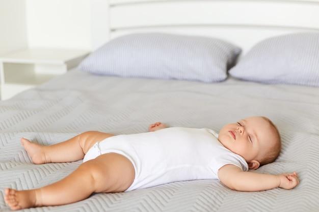 Bebê tranquilo deitado em uma cama enquanto dorme em uma cama macia em um cobertor cinza, bebê vestindo macacão branco dorme sozinho dentro de casa, infância.