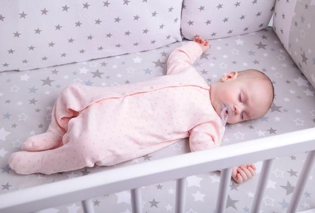 Bebê tranquilo, deitado em uma cama enquanto dorme, vista superior