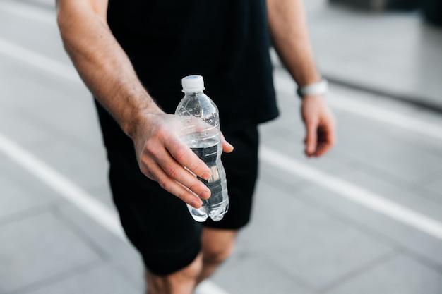 Bebe um pouco de água! a mão do homem estende uma garrafa plástica de água. asfalto cinza no fundo. homem em traje esporte preto, movimentando-se. hora de hidratação! treino lá fora.