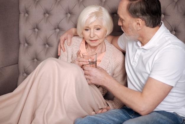 Bebe um pouco de água. retrato de uma senhora idosa preocupada sentada coberta com um cobertor quente e segurando um copo de água perto de seu marido apoiando.