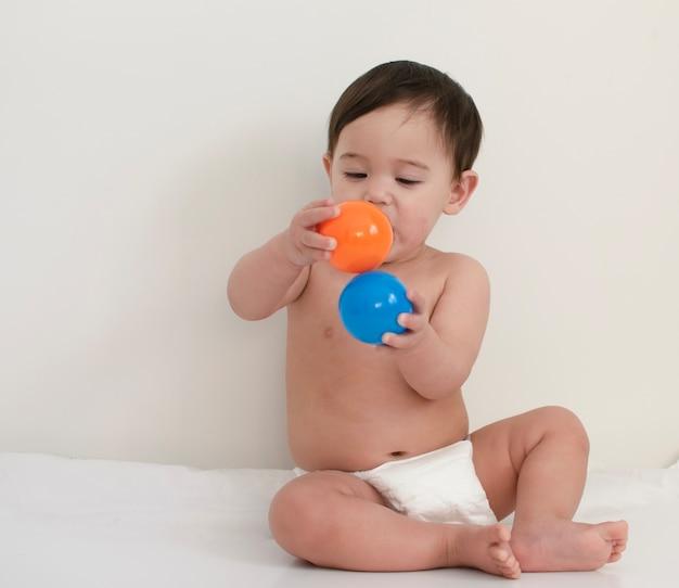 Bebê usa fralda branca de eliminação está jogando com bolas de plástico coloridas