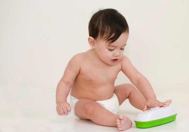 Bebê usa fralda branca está jogando com brinquedo